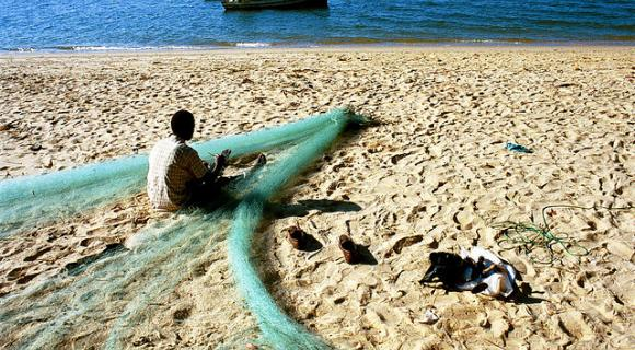 Fisherman repairing his nets on the beach. Mozambique.